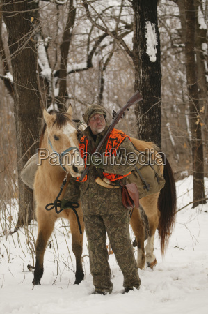muzzleloader hunter with horse hunting in