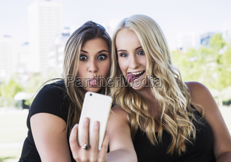 two girlfriends taking self portraits of