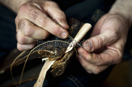 a mans hands sewing leather pelotas