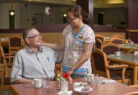 senior citizen and caregiver in cafeteria