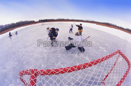boys playing hockey on frozen pond