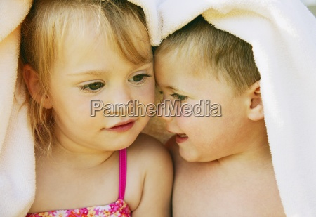 two kids snuggle under a towel