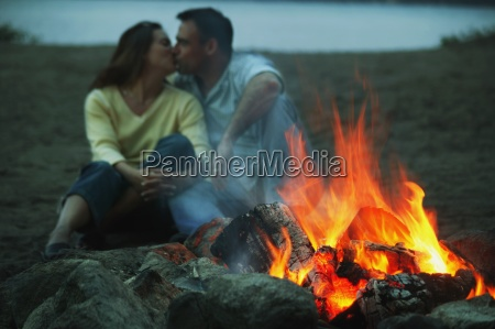 couple keep warm by campfire