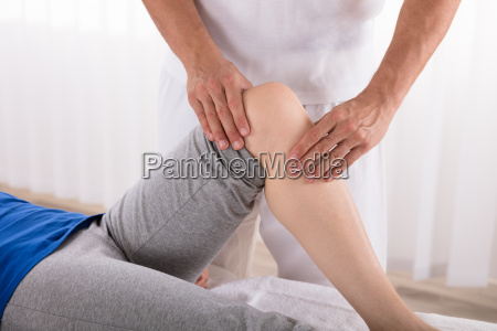 physiotherapist giving knee exercise to woman