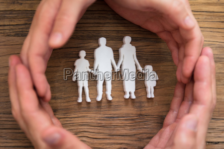 couples hand protecting family figures
