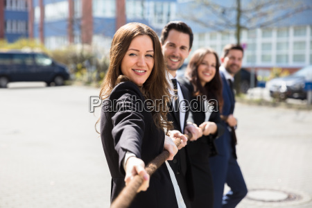 businesspeople playing tug of war
