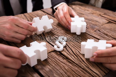 businesspeople hand holding jigsaw puzzle