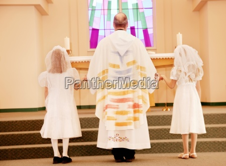priest with children doing first communion