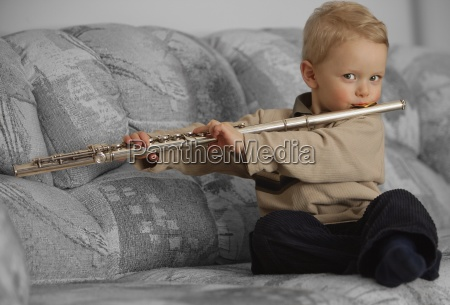 young boy playing a flute