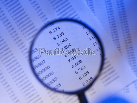 magnifying glass and sheet of numbers