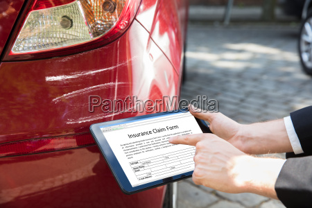 person filling insurance claim on tablet