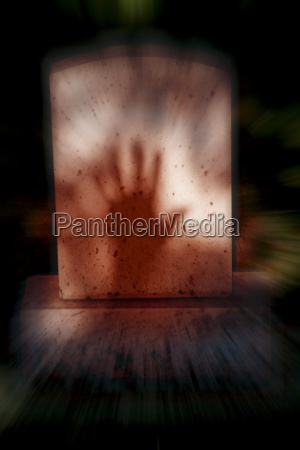 shadow of hand on tombstone