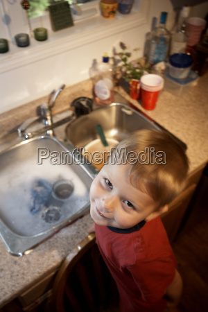 boy standing on chair at kitchen