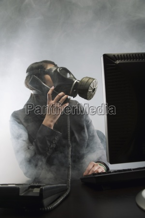 businessperson wearing gas mask in smoky