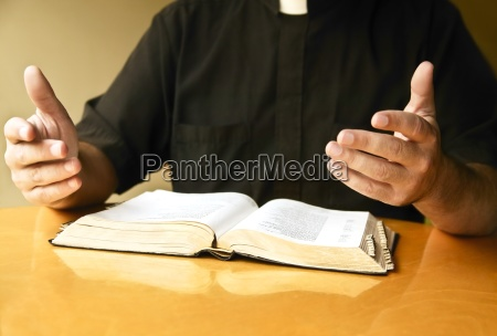 a priest reading the bible
