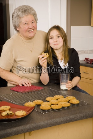 grandmother and granddaughter eating cookies