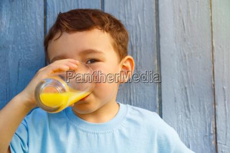 child little boy drinks orange juice