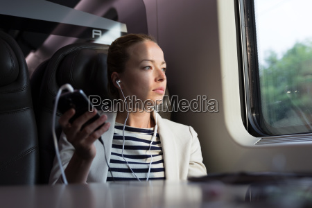 thoughtful businesswoman listening to podcast on