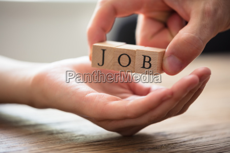 businessperson giving wooden block with job