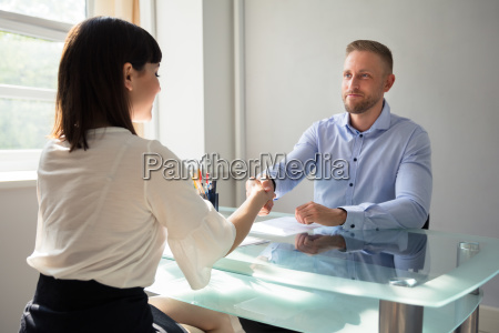 smiling young businessman shaking hand with