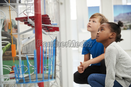 two kids kneeling and looking at