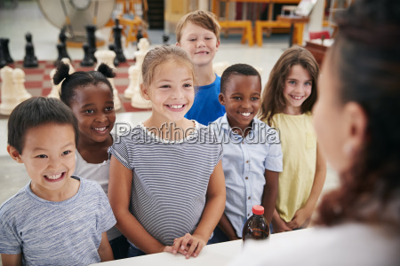 group of smiling kids listening to