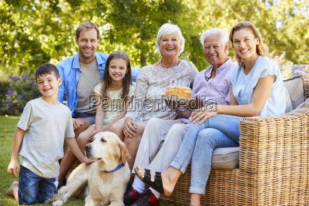 three generation family petting a dog