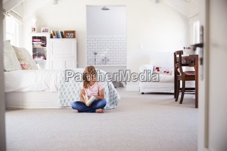 young girl reading a book alone