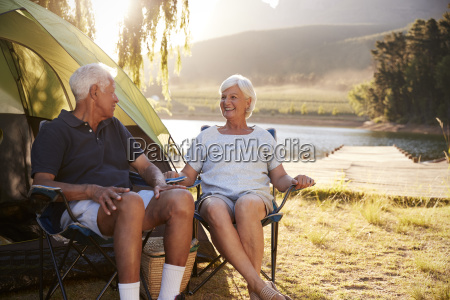 senior couple enjoying camping vacation by