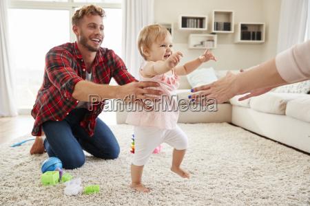 toddler girl walking from dad to