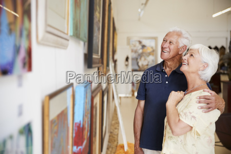 senior couple looking at paintings in