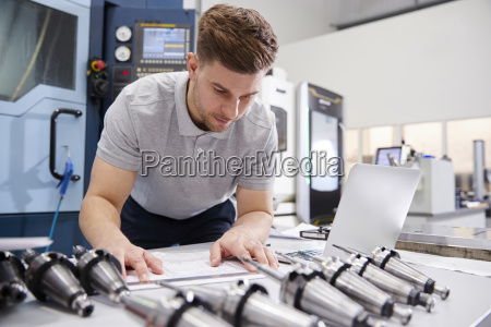 male engineer measuring cad drawings in