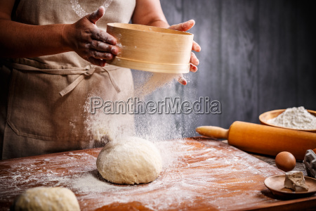 woman hands sifting flour