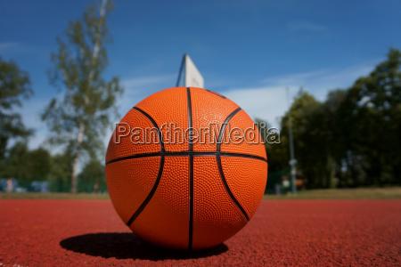 orange basketball against the blue cloudy