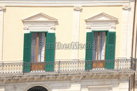 old window with opened green shutters