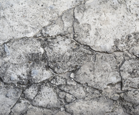old gray cement wall with cracks