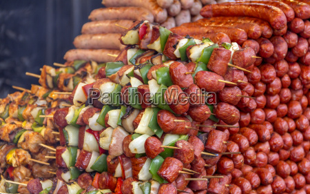 various barbecued sausages and meat skewers
