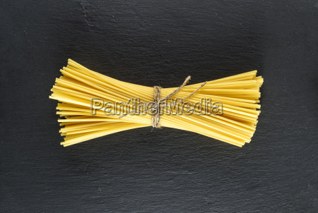 raw spaghetti tied with a rope