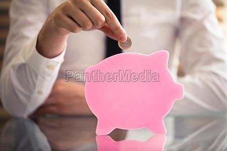 businessperson inserting coin in flat piggybank