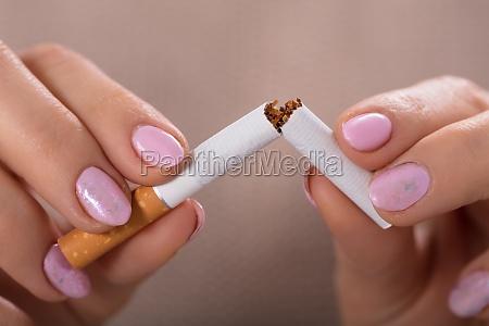 woman holding broken cigarette