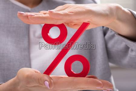 woman holding percentage symbol