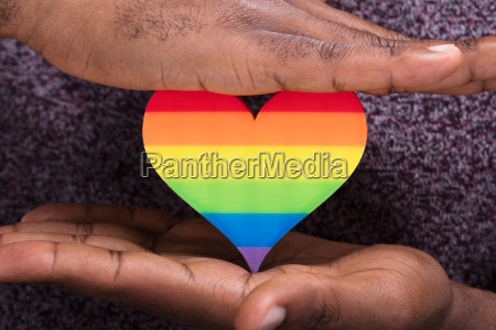 mans hand protecting colorful heart