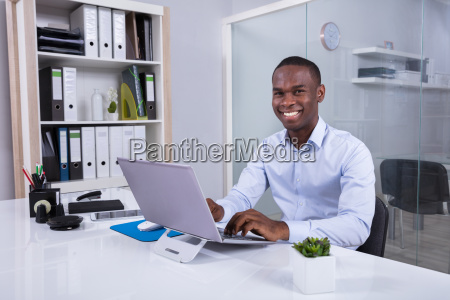 portrait of smiling businessman at workplace