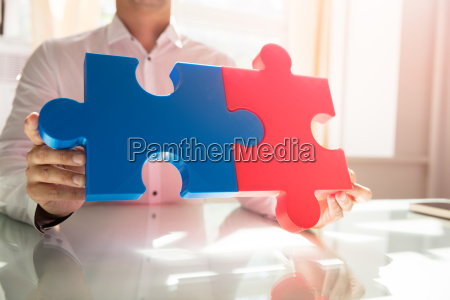 businessman connecting two jigsaw puzzles