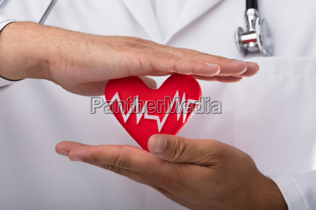 doctor holding red heart rate