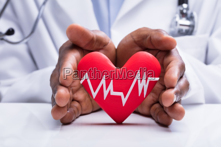 doctor protecting heart with heartbeat pulse