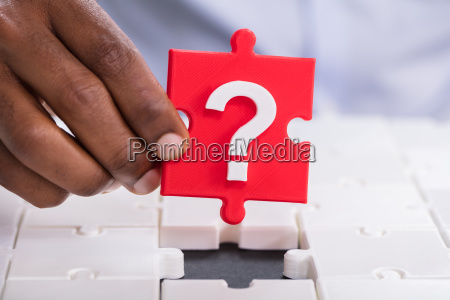 hand holding question jigsaw puzzle