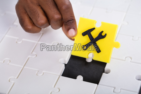 hand holding work tool jigsaw puzzle