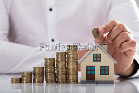 businessman holding coin over house model