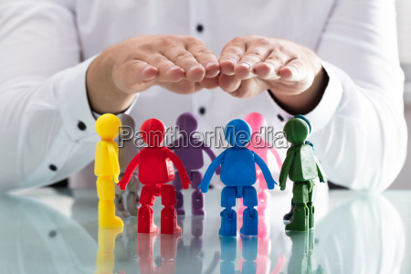 person protecting multi colored human figures